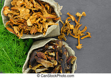 Top view composition of dry boletus and chanterelles mushrooms placed in canvas with dill and parsley broom on black stone background surface with copy space