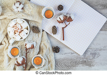 Top view composition with cup of coffee and marshmallow, pumpkin, candles, cotton plant flower branches, notepad and copy space