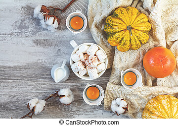 Top view composition with cup of coffee and marshmallow, pumpkin, grapefruit, cotton plant flower branches and copy space