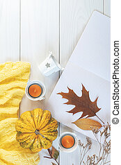 Top view composition with pumpkin, cotton plant flower branches, notepad and copy space.