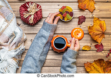 Top view composition with woman's hands in gray sweater, pumpkin styled cup of coffee and autumn themed decoration, fallen leaves and candy on wooden background. Flat lay, copy space