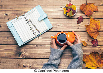 Top view composition with woman's hands in sweater, pumpkin styled cup of coffee and autumn themed decoration, fallen leaves and notebook on wooden background. Flat lay, copy space
