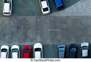 Top view concrete car parking lot. Aerial view of car parked at car parking area of apartment. Outdoor parking space with empty slot. One way traffic sign on road. Above view outside car parking lot.