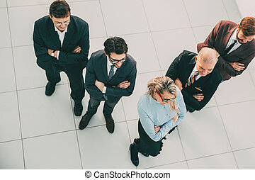 top view. confident business woman standing in front of her colleagues.