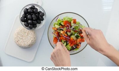 Top view. cooking vegetarian low calorie Greek salad, woman's hands tossing the a salad. 4K