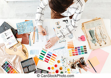 Top view cropped photo of young woman fashion illustrator drawing