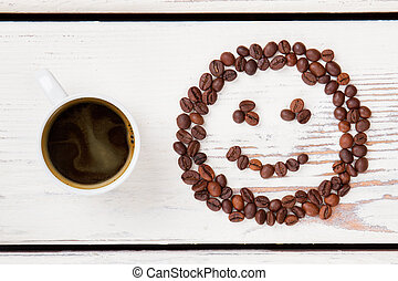 Top view cup of hot coffee and beans in a shape of smiley face.