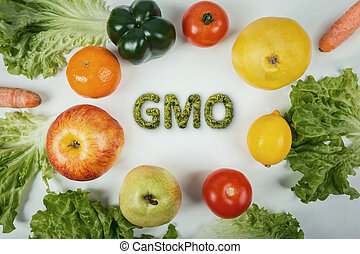 Top view different GMO fruits and vegetables arranged on the table. Non organic food dangerous nutrition for human health. Fresh crop genetically modified. DNA manipulation and biotechnology concept.