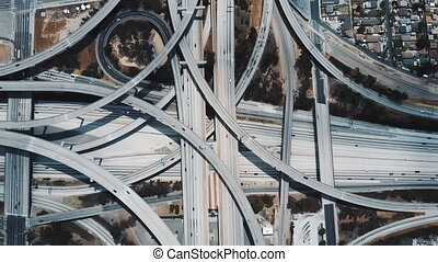 Top view drone rising above incredible complex highway junction in Los Angeles with traffic moving on multiple levels.