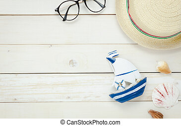 Top view essential travel summer items. The boat eyeglasses hat shell on white wooden background.