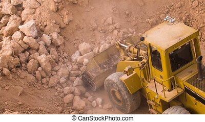 top view excavator loading crushed rock on dumper truck
