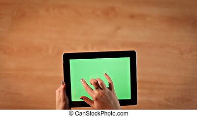 Top view female hands drawing on green screen digital tablet