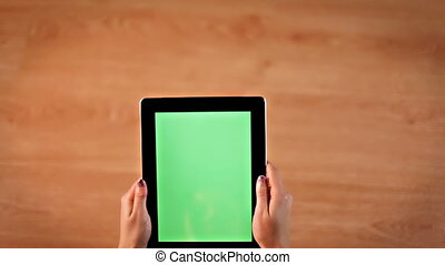 Top view female hands scrolling, zooming images on digital tablet vertical