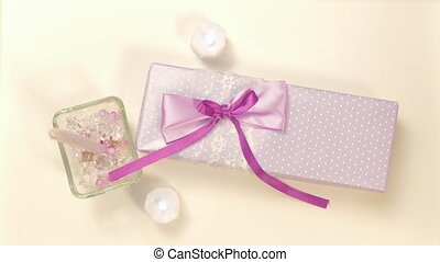 Candles and decorative stones around. Gift in wrapping paper tied with a purple ribbon. A surprise on a birthday or on Valentine's day, new year or Christmas.