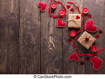 Festive composition. Hearts from red felt, boxes handmade on a wooden table