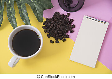 Top view flat lay of coffee cup with blank notebook, coffee beans, leaves on color background.