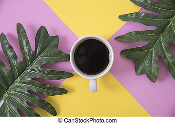 Top view flat lay of coffee cup with green leaves on color background.