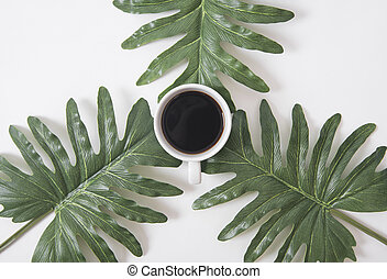 Top view flat lay of coffee cup with green leaves on white background.