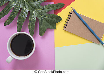 Top view flat lay of coffee cup with pencil, notebook, leaves on color background.