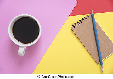 Top view flat lay of coffee cup with pencil, notebook on color background.
