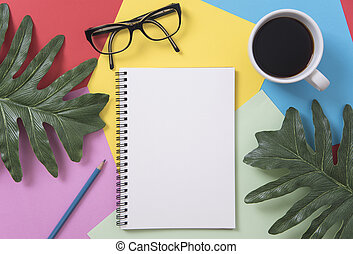 Top view flat lay of coffee cup with sunglasses, pencil, notebook, leaves on color background.
