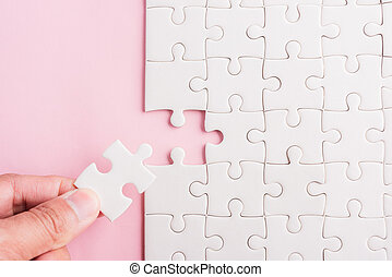 hand-holding last piece white paper jigsaw puzzle game last pieces