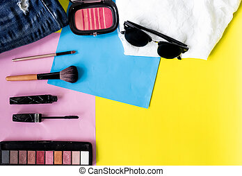 top view flat layer beauty make up set, mascara, brushes, eye shadow palate, and brush on, on two tone background