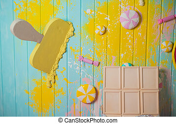 Top view, Flatlay template design of a bar of white chocolate and ice cream on mint yellow wooden background with copy space. Top view, Flatlay template design a group of sweets