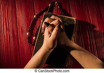 Top view folded young demale hands onholy bible cover with rosary.