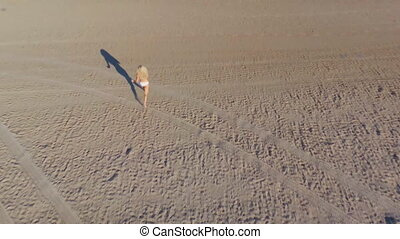 Top view from back aerial shooting from flying drone of a blonde girl in white bikini runs along the sand of the beach into the water. Long shadows. Early morning. No sound