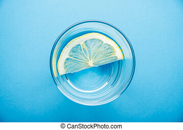 glass of water with slice of lemon on blue background