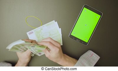 Green screen. Male hands counting money - Top view. Green...