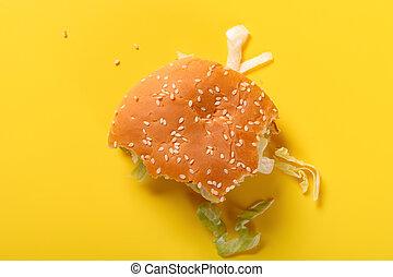 top view half eaten hamburger on a yellow background