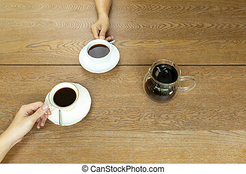 Top view hand holding a cup of coffee with coffee pot on wooden table.