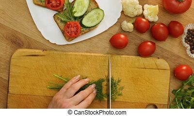 Top view hands cuts dill making vegan sandwich