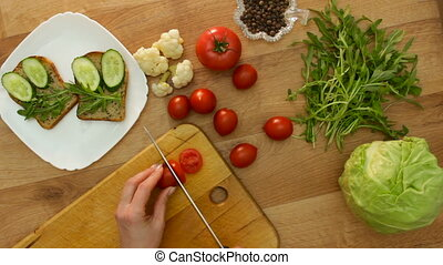 Top view hands cuts tomato making vegan sandwich