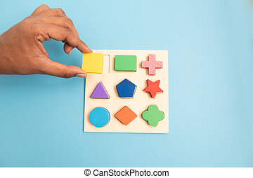 Top view Hands Picking up one Colorful Wooden building blocks in different shapes on blue background.