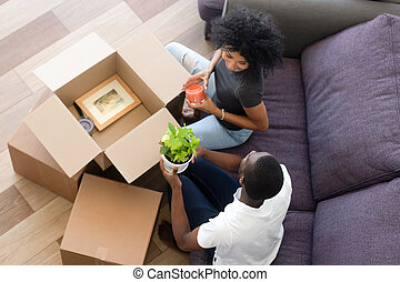 Top view happy African American couple in love unpack boxes at home