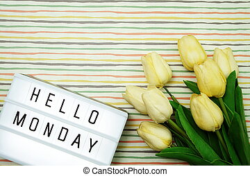 Top view Happy Monday Text in Light box flat lay with tulip flower bouquet