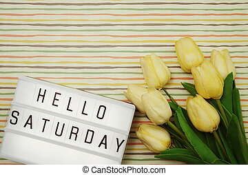 Top view Happy Saturday Text in Light box flat lay with tulip flower bouquet