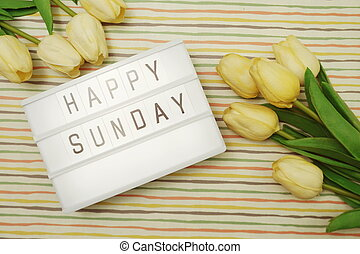 Top view Happy Sunday Text in Light box flat lay with tulip flower bouquet