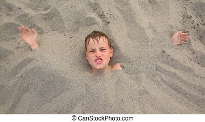 Top view head of boy lies smiles buried up with sand