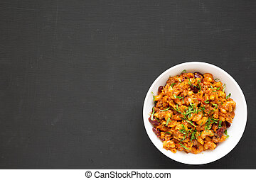 Top view, homemade Chili Mac and Cheese with Parsley in a white bowl over black background, top view. Flat lay, overhead, from above. Space for text.
