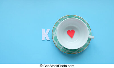 Top view image cup with phrase: THANK, next and little red heart on blue background. Stop motion. HD 1920x1080