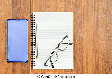 Top view image of open notebook with blank page and cellphone on wooden table