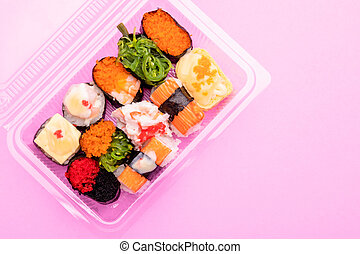 Japanese food (sushi) in clear plastic food box on pink background