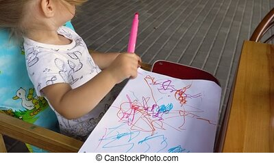 Top view. Little girl drawing messily in album - Top view....