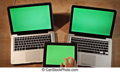 Top view man scrolling and zooming images on digital tablet lying on two laptops