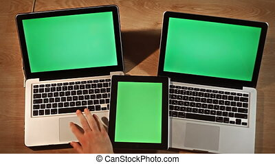 Top view man using digital tablet and two laptops