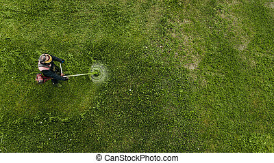 Top view man worker cutting grass with lawn mower.